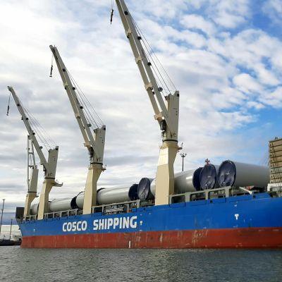 Lastfartyg med blå sidor i hamn under en blå och delvis molntäckt himmel. Ett kinesiskt fartyg lastat med delar till vindkraftverk i Vasa hamn.