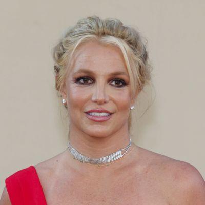 Britney Spears tittar åt sidan och ler på röda mattan.