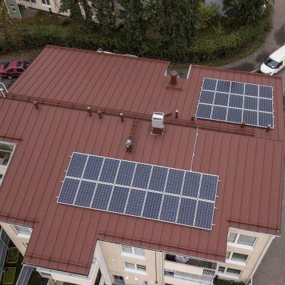 Aurinkopaneelit kerrostalon katolla.