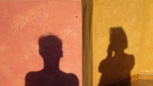 En kvinnas och en mans skugga på en vägg