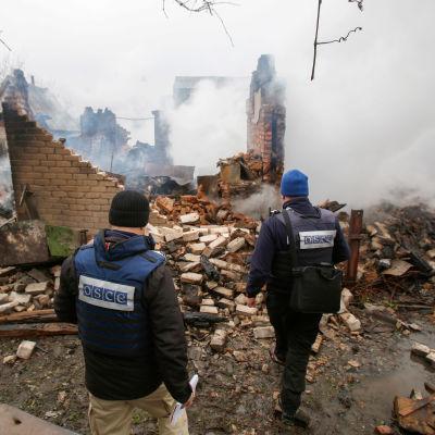 OSSE-observatörer inspekterar en förstörd byggnad i Avdiivka 25.2.2017