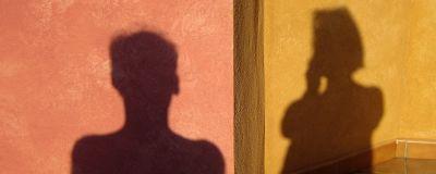 En kvinnas och en mans skugga på en vägg.