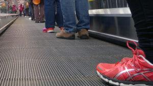 Rulltrappa utan trappsteg, mänskors fötter syns