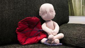 Synnytysvalmennuksessa apuna käytettävä sikiötä esittävä kankainen nukke, istukka ja napanuora. Nukke istuu sohvalla.