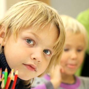 Kuvassa poika katsoo suoraan kameraan. Etualalla nippu värikyniä.