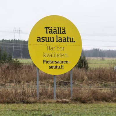 Keltaisessa peltomaisemaan sijoitetutssa kyltissä lukee: Täällä asuu laatu.