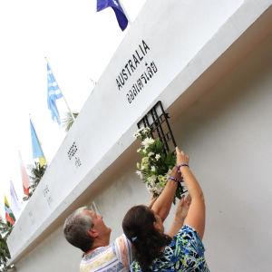 Australier hänger blommor på en minnesplats på Phuket island, Thailand.