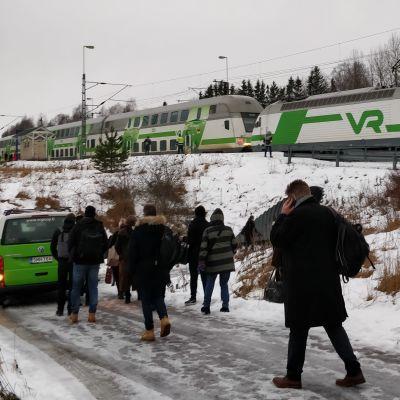 Tågpassagerare lämnar ett tåg som gått sönder.