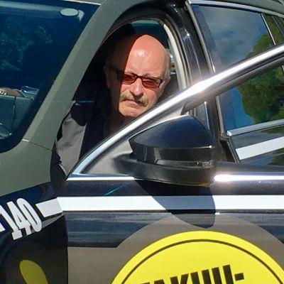 Kajaanin taksiautoilijoiden puheenjohtaja Erkki Korhonen istuu taksinsa kyydissä.