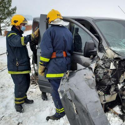 Två brandmän vid en krockskadad skåpbil.