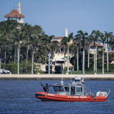 Kustbevakningens lilla röda båt med beväpnade vakter skyddar strandlilnjen till rpesidnetens lyxklubb som skymtar bakom palmerna.
