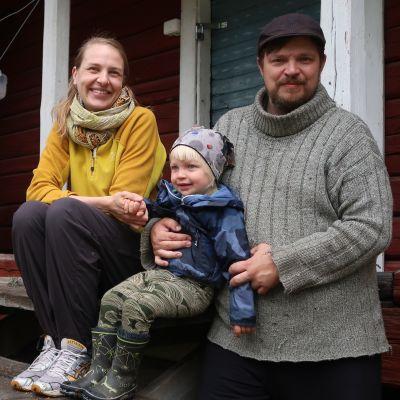 Anna Liljeroos, Timo Sinnemäki ja pikkuinen Emil istuvat metsäpeurapaimenten torpan pihalla