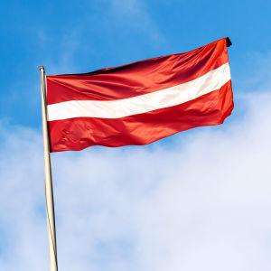 Lettlands flagga framför blå himmel.