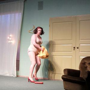 Elina Knihtilän näyttelemä nainen seisoo alusvaatteisillaan, korkokengät jalassa, ja näyttää pelästyneeltä.