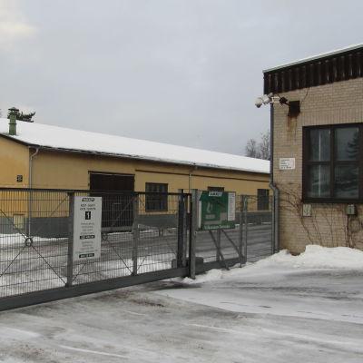 Två fabriksbyggnader och ett staket av metallnät. Stängd port till området. Snö och vinter.