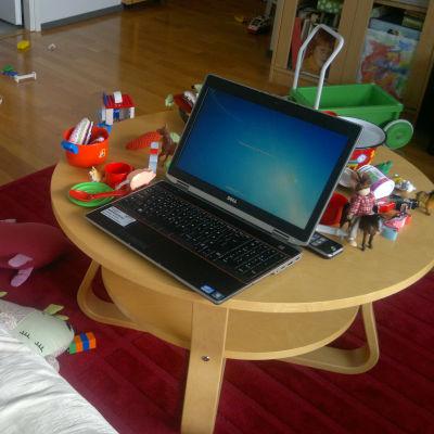 Laptop i vardagsrum fyllt av leksaker.