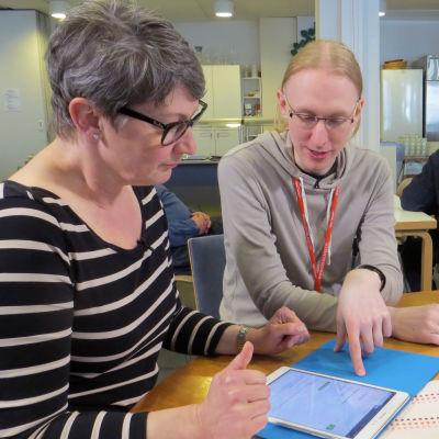 Digineuvoja Juha Koivunen työssään Lohjan Apuomena-järjestön tiloissa, neuvottavana keski-ikäinen nainen.