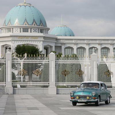 Sininen Volga-auto on suuren sinikupolisen palatsin edustalla.