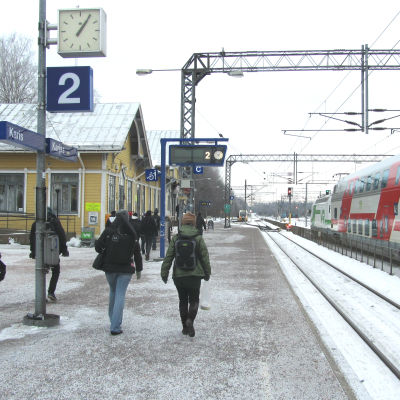 Människor går på perrongen på järnvägsstationen i Karis.