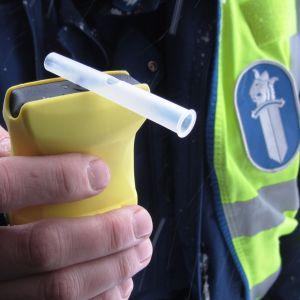 Polis håller i alkometer.