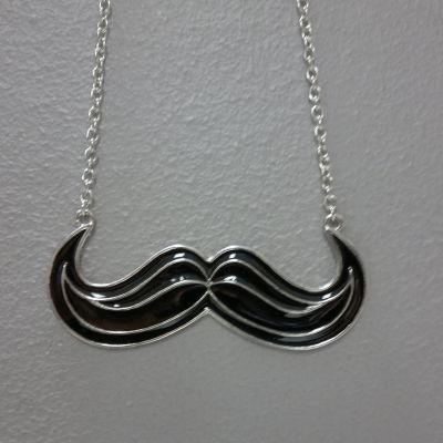 En Movember-mustasch som hängsmycke.