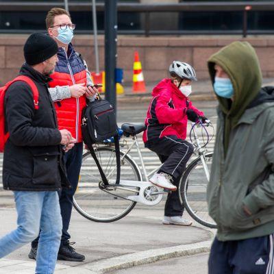 Fotgängare och en cyklist med masker ute i stadstrafiken.
