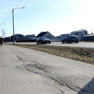 Sprickor på sliten cykelväg.