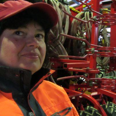 Förvaltare Marina Bergheim-Ahlqvist vid såmaskinen, som väntar på att komma på åkrarna.