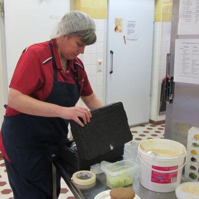 Kosthållschef Agneta Lindroos packar ner en modell av Raseburgaren.