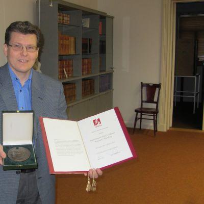 Museichef Dan Lindholm visar upp Helene Schjerfbeck-medaljen och diplomet Ekenäs museicentrum EKTA fick av Svenska Kultrufonden.