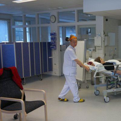En sjukskötare och en närvårdare samarbetar vid den geriatriska polikliniken
