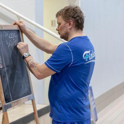 Uintivalmentaja Marko Malvela piirtää harjoitusohjelmaa liitutaululle.