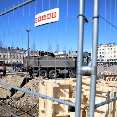 Kuva Mikkelin torilta, jonne rakennetaan torilavaa. Kuvassa rakennustyömaa-aita, jonka takana tehdään perustustöitä.