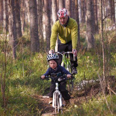 Isä ja poika pyöräilemässä metsässä