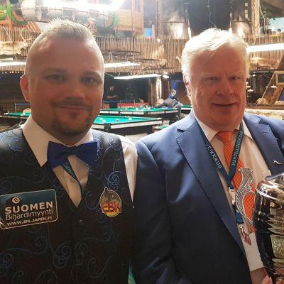 Kilpailunjohtaja Erkki Närä pitää käsissään voittopokaalia. Kilpailijat Tuomas Komi ja Ville Pasanen tavoittelevat mestaruutta.