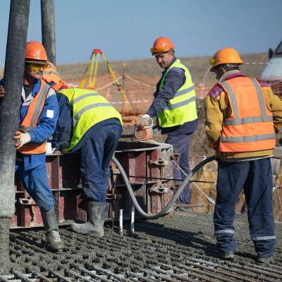 Miehet rakentavat tuulivoimalan perustaa.