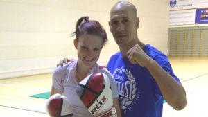En bild på Emmy Erroll med boxningshandskar och det röda håret i hästsvans. Hon står brevid boxaren Amin Asikainen som har en blå t-skjorta och lyft näve.