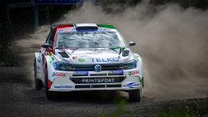 En rallybil kommer i hög hastighet på en grusväg.