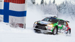 En rallybil kommer fort i en kurva på snötäckt väg.