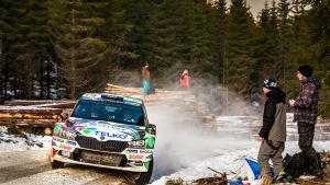 En rallybil susar fram på en snötäckt grusväg.