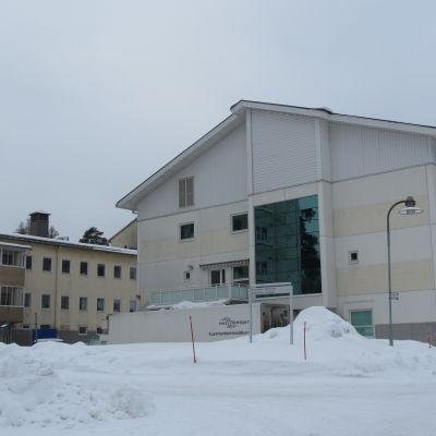 Vita våningshus vid Raseborgs sjukhus i ett vinterlandskap.