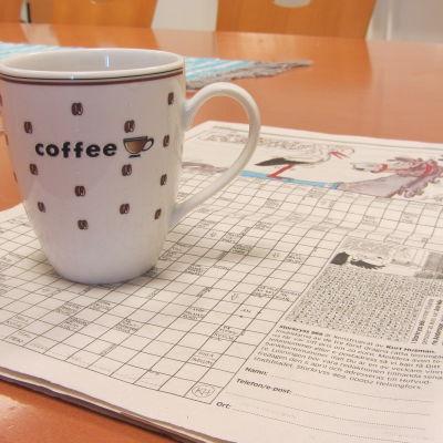 Ett korsord och en kaffekopp på ett köksbord.