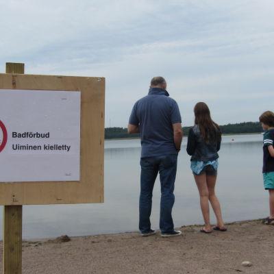 familj på strand invid skylt med badförbud