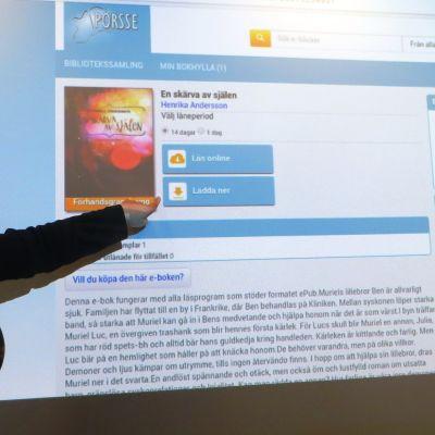 Bibliotekarie Tove Selkälä, e-boksansvarig vid Borgå stadsbibliotek, visar hur lätt man lånar e-böcker