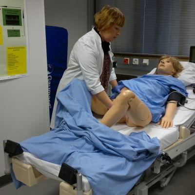 Docka och sköterska i simuleringsrummet.