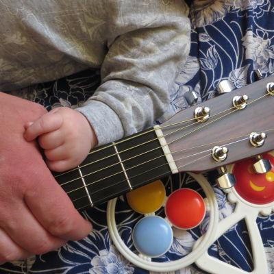 händer på en gitarr