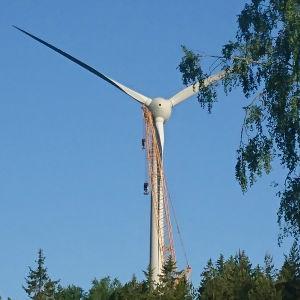 En lyftkran bredvid en vindmölla.