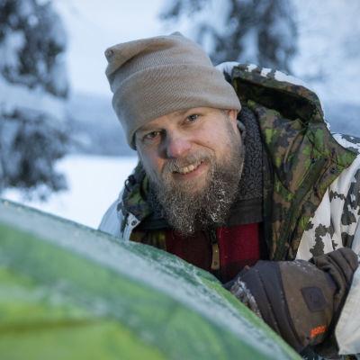 Hymyilevä Mikko Kettunen pystyttää vihreää telttaa lumisessa metsässä.