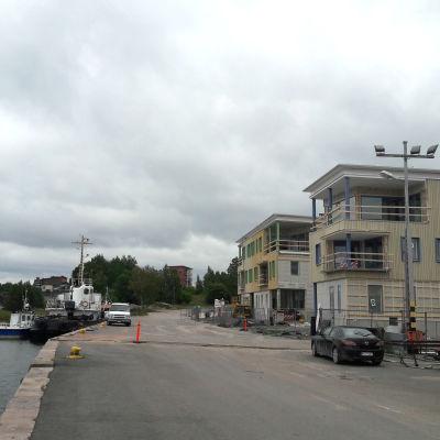En kajkant där ett större fartyg står ankrat. Till vänster syns nybyggda bostadshus.