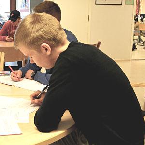 Elever sitter vid ett bord och skriver på papper